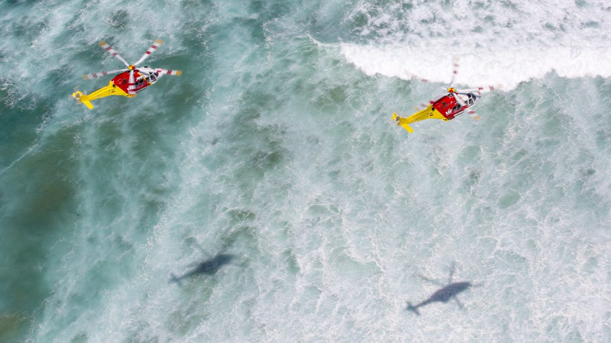 two westpac rescue helicopters flying over the ocean