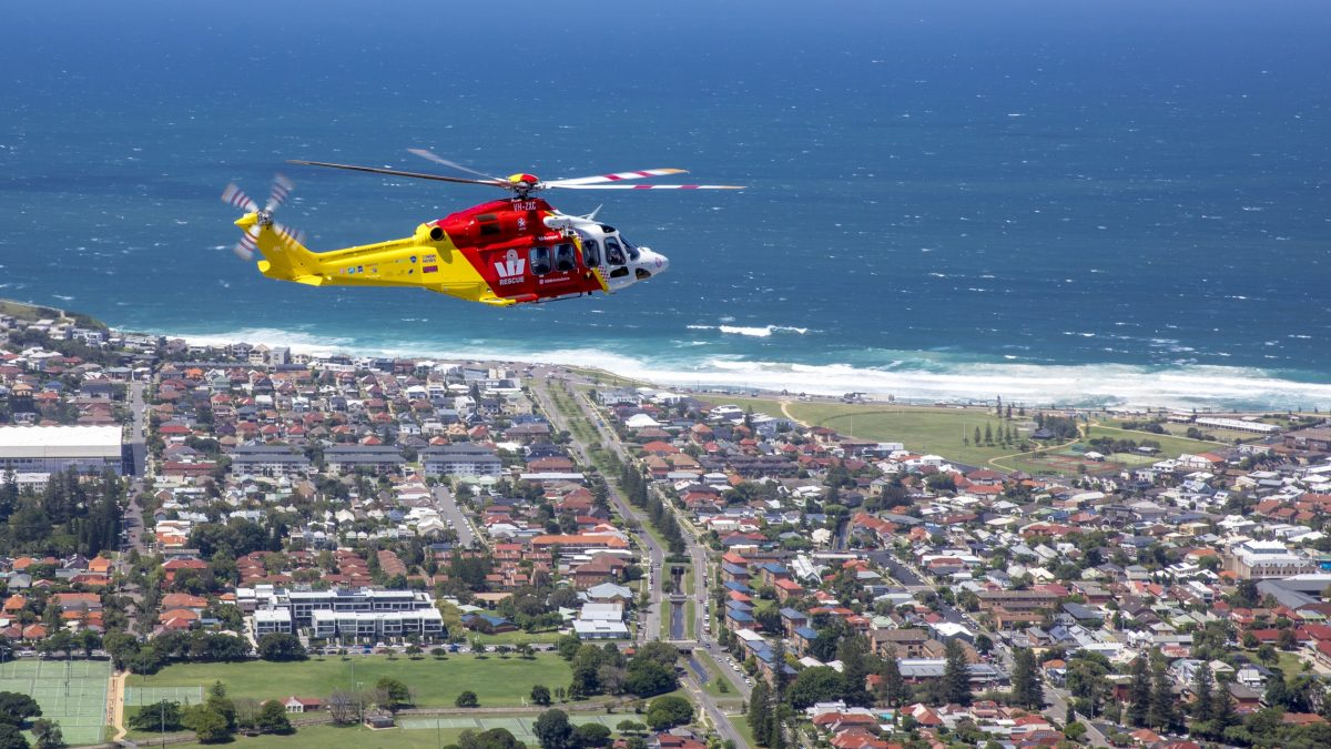 Westpac rescue helicopter flying over Bar Beach coastline