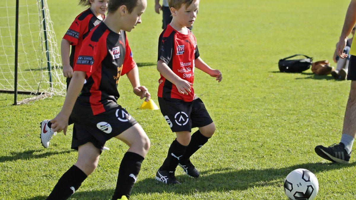 arnetts football teammates kicking ball