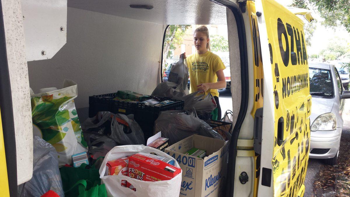 OzHarvest worker loading food donations into van